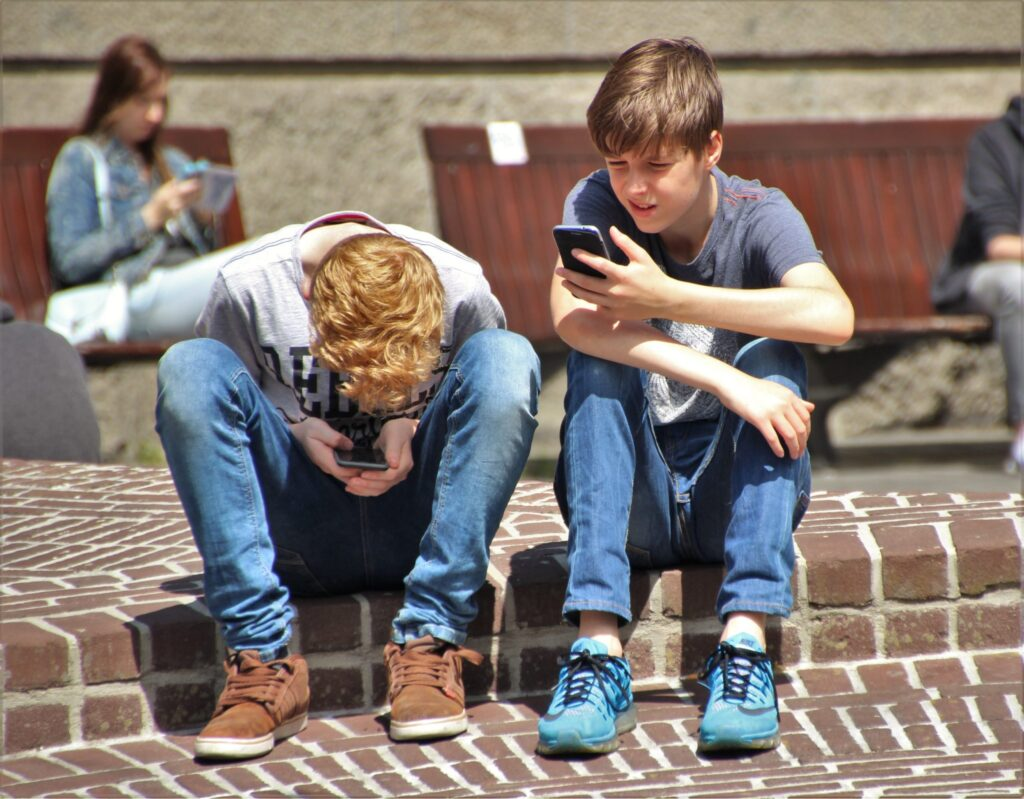 Two boys sitting outside with mobile phones