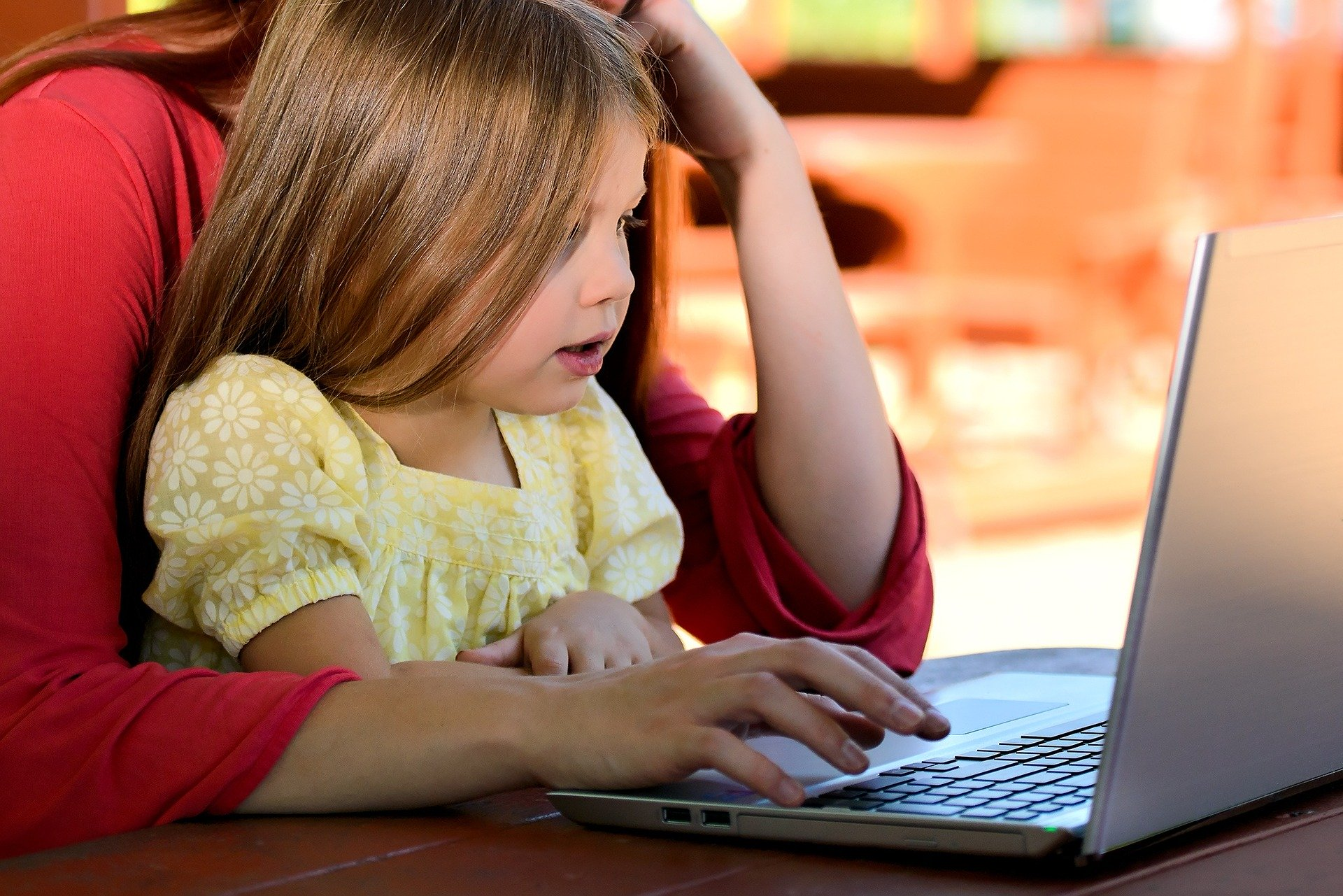 Child at laptop with mother