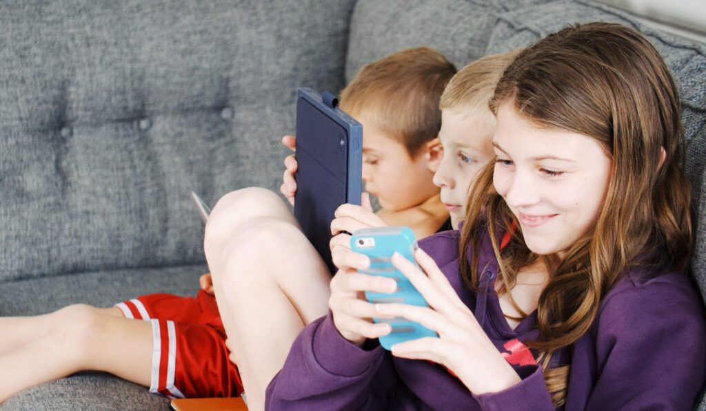 Young children on sofa with mobile phones