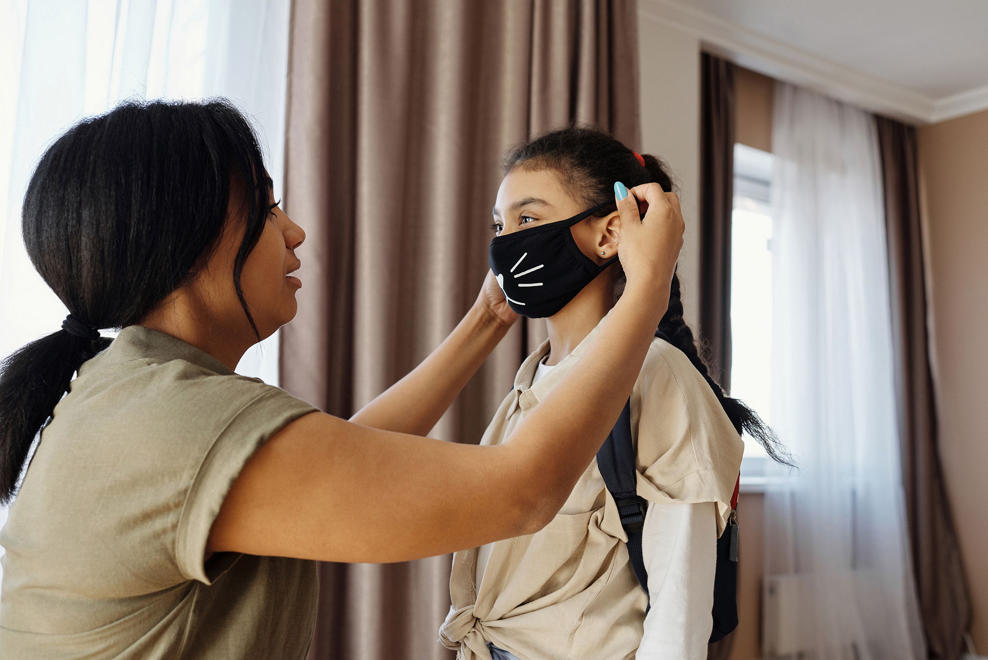 Mother putting a face mask on a child