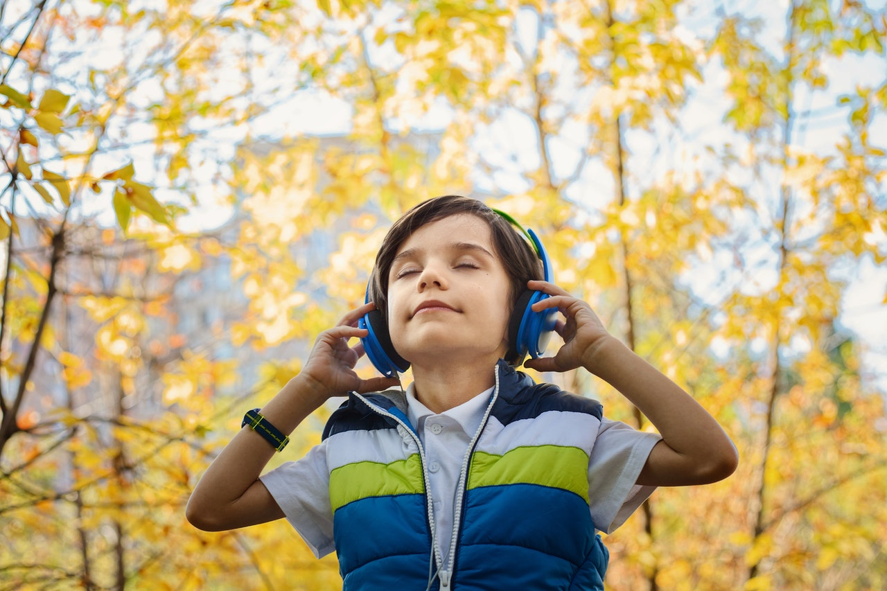 Child with headphones walking