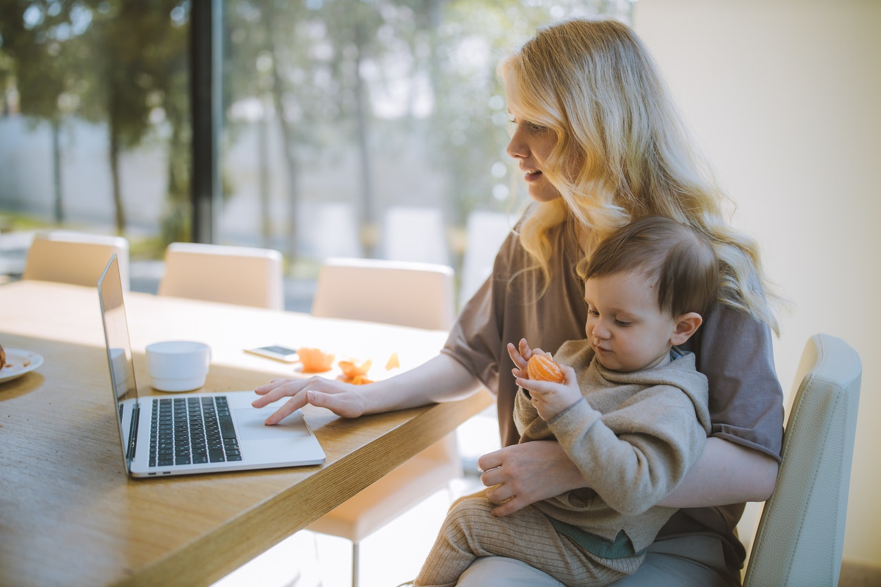 Mother working on laptop with young child on lap