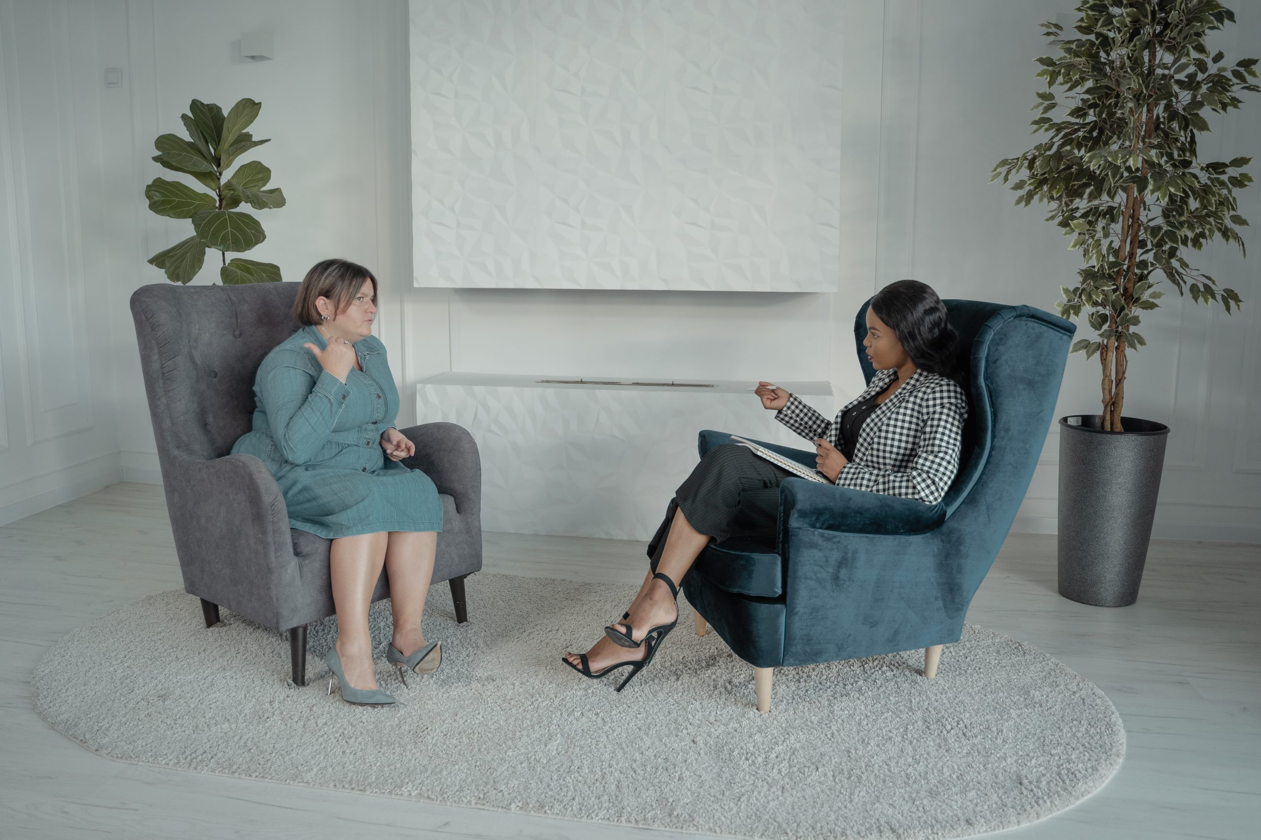 Two women sitting on chairs facing one another and one woman taking notes.