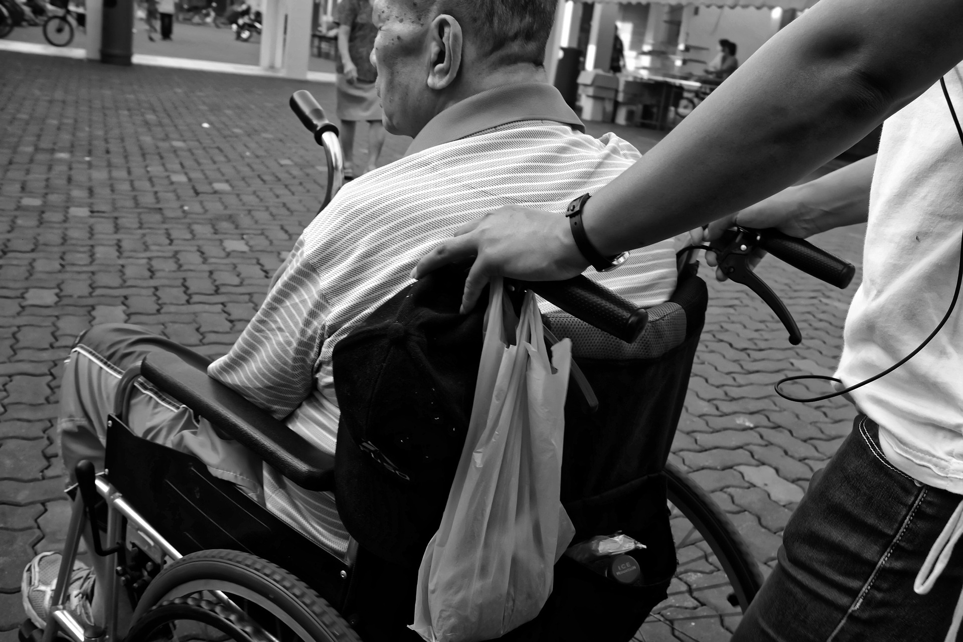 A man in a wheelchair being pushed by another person