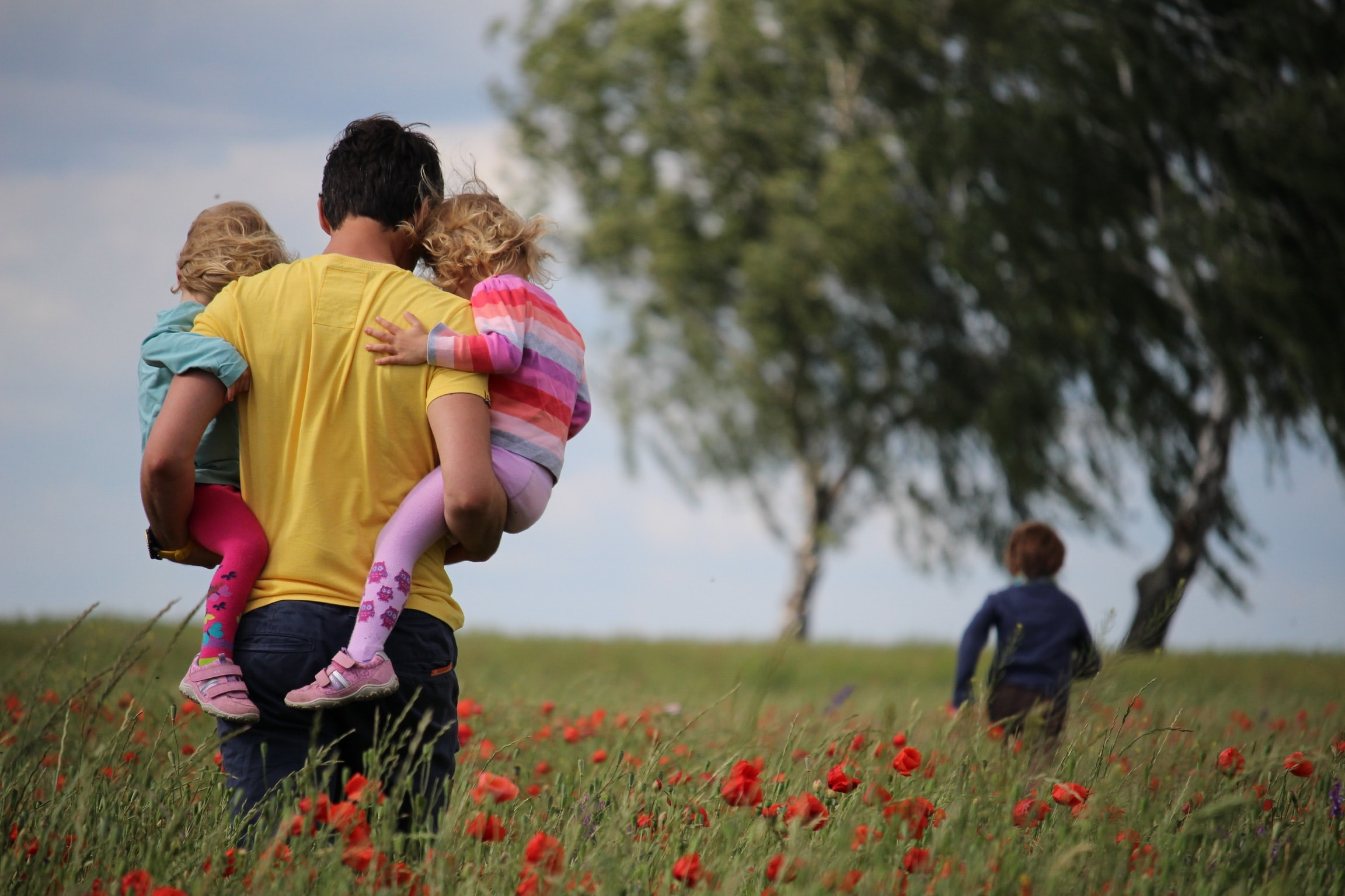 A father holding 2 kids and another child running in the distance